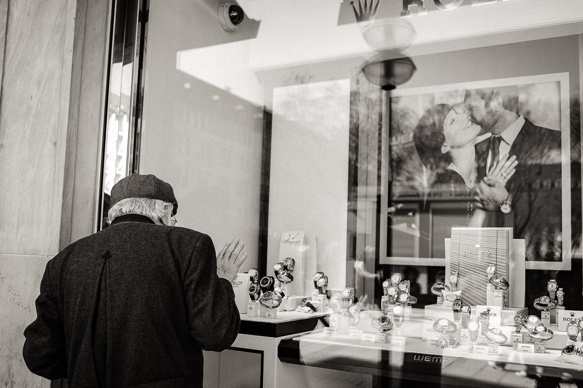 Old man looks into shop window containing watches and an image of a younger couple